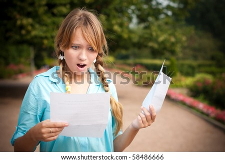 beautiful young student girl shocked by message she is reading. She is standing in campus park, holding paper with message and envelope. - stock photo