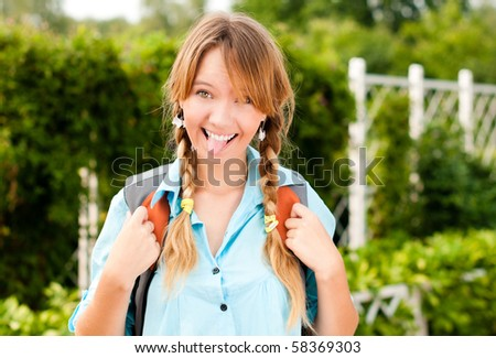 beautiful young student girl with backpack standing in campus park, showing her tongue, smiling and looking into the camera - stock photo