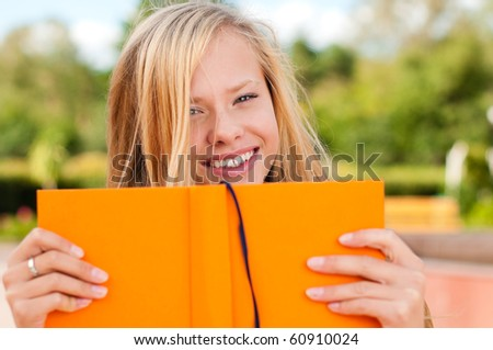 beautiful young student girl, with opened orange book in front of her, looking into the camera - stock photo
