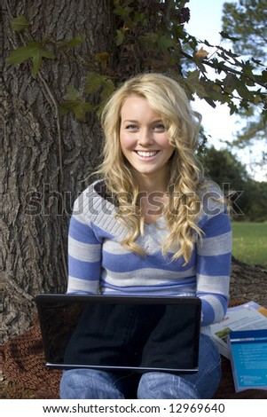 beautiful young student typing on a laptop - stock photo