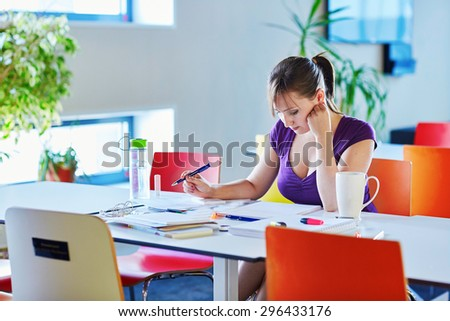Beautiful young student with books and papers, studying in the library or classrom - stock photo