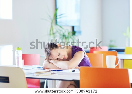 Beautiful young student with books and papers, studying in the library or classroom, tired and sleeping on the table - stock photo