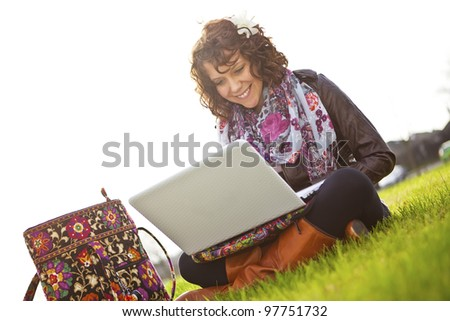 Beautiful young student with long curly hair sitting on grass with laptop