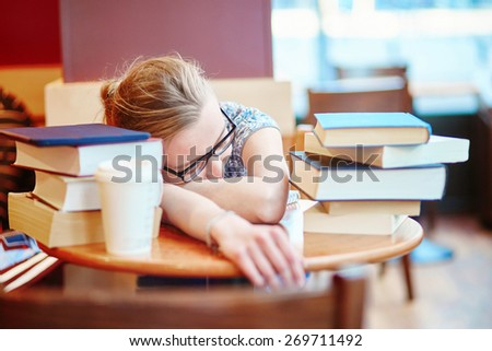 Beautiful young student with lots of books, preparing for exams in a cafe and sleeping on the table tired. Shallow DOF - stock photo