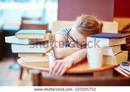 Beautiful young student with lots of books, preparing for exams in a cafe and sleeping on the table tired. Shallow DOF