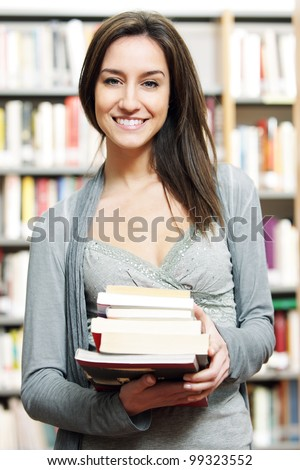 beautiful young student with pile of books - stock photo