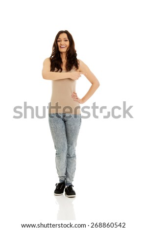 Beautiful young student woman pointing somewhere. - stock photo
