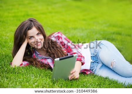 Beautiful young student woman study with tablet in park.
