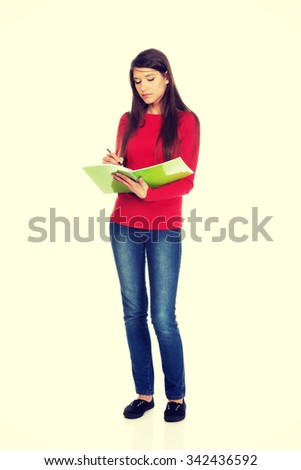 Beautiful young student woman writing in her note. - stock photo