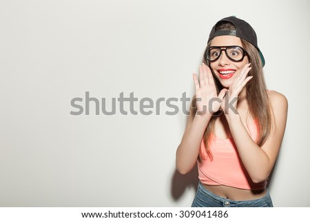 Beautiful young styled woman is standing and looking forward with shock. She is raising her arms to her face and smiling. The woman is wearing cap and eyeglasses. Isolated and copy space in left side - stock photo