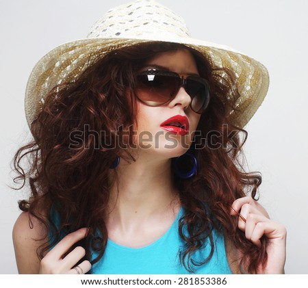 Beautiful young surprised woman wearing hat and sunglasses
