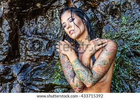 Beautiful young tattooed woman posing against a wall of wet, black volcanic rock - stock photo