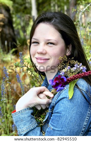 Beautiful young teen enjoy a field of wildflowers in Mexico.  She is kneeling and holding a small bouquet against her shoulder.  She is wearing denim. - stock photo