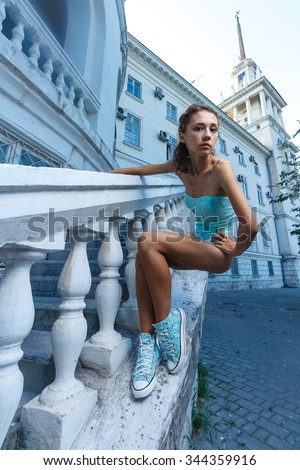 Beautiful young teen girl in bodysuit posing during city fashion shoot with classical building at background