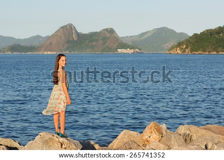 Beautiful young teen girl smiling, standing on stones near sea in dress with long brown hairs in sunset light. Selective focus - stock photo