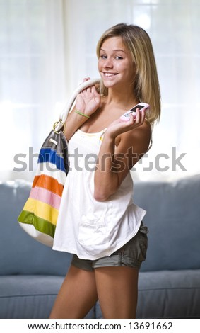 Beautiful young teenage girl holding cell phone