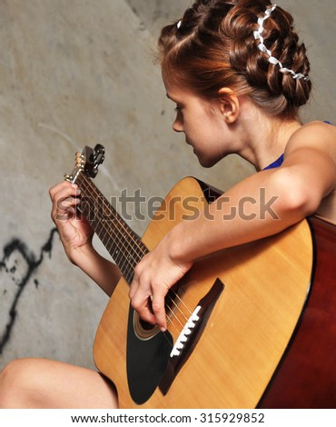 Beautiful young teenage girl with guitar musical instrument guitar. Grunge background. - stock photo