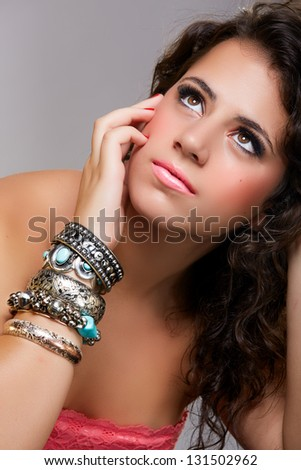beautiful young teenage girl with long brown curly hair wearing turquoise bracelets on gray studio background