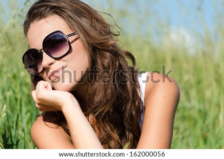 Beautiful young teenage woman wearing sun glasses on summer day outdoors