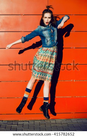 Beautiful young teenager hipster girl having fun, posing and jumping near urban red wall background in skirt and jeans jacket on the sunset. - stock photo