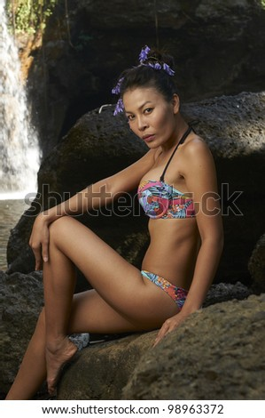 Beautiful young Thailand model wearing colorful bikini in front of scenic waterfall in lush jungle on summer day. - stock photo