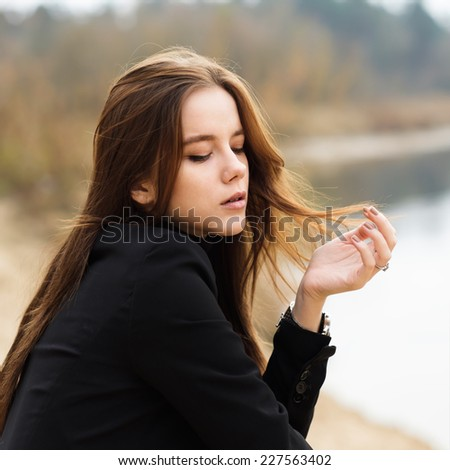 beautiful young thoughtful girl in a black coat - stock photo
