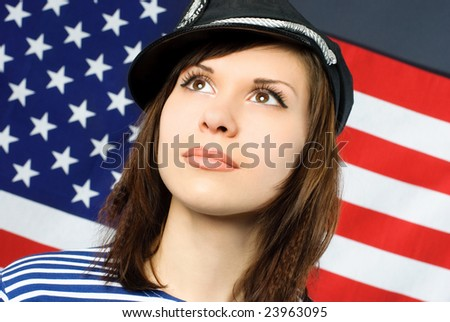 beautiful young thoughtful sailor standing opposite an American flag - stock photo