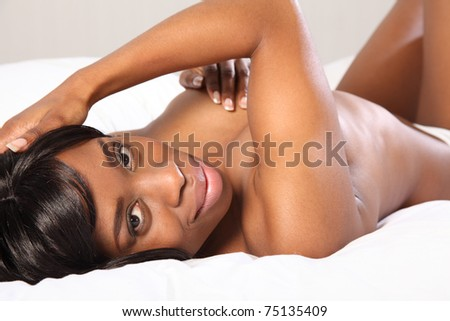 Beautiful young topless black woman lying casually on her back in bed, very relaxed looking back with a happy smile. - stock photo