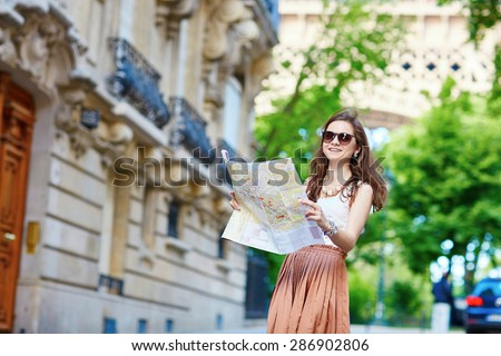 Beautiful young tourist in long skirt on a street of Paris near the Eiffel tower on a summer day, looking at the map and planning her itinerary - stock photo