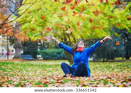 Beautiful young tourist in Paris on a fall day, sitting on the ground in the Luxembourg garden and throwing up colorful autumn leaves - stock photo