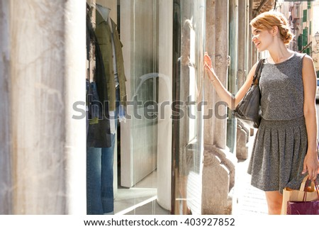 Beautiful young tourist woman carrying shopping bags walking in city fashion stores, joyfully smiling looking at shop windows, sunny outdoors. Consumer girl, exclusive expensive lifestyle exterior. - stock photo