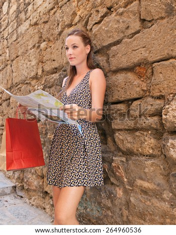 Beautiful young tourist woman visiting a destination city with rough old textured stone wall in a narrow street, using a map, sightseeing on holiday. Travel and shopping on vacation, outdoors. - stock photo