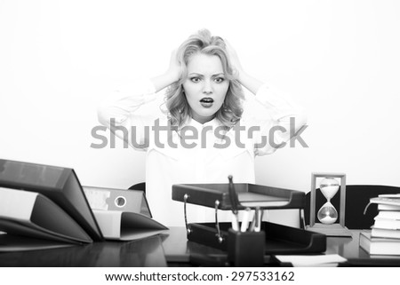 Beautiful young upset secretary girl with curly hair has a lot of work sitting at table with many folders documents and office appliances holding head black and white, horizontal picture - stock photo