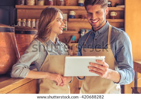 Beautiful young waitress and handsome young waiter in aprons are using a tablet, talking and smiling while standing in the cafe