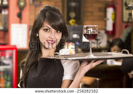 beautiful young waitress girl serving a drink holding tray - stock photo
