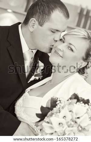beautiful young wedding couple, bride with bouquet kissed by her groom, black and white tone