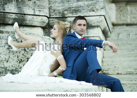 Beautiful young wedding couple of sensual blond girl in white dress and shoes and man in blue suit with red bow tie sitting near stone building outdoor, horizontal picture - stock photo