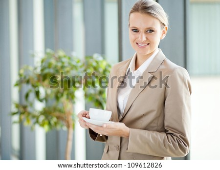 beautiful young white collar worker having coffee during break - stock photo