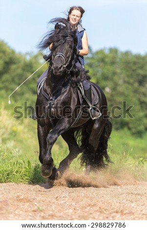 Beautiful young wioman riding black stallion. - stock photo