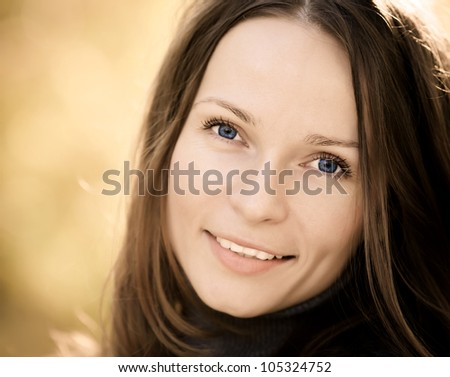 Beautiful young woman against blurred autumn background