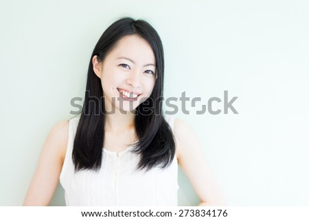 beautiful young woman against light green background - stock photo