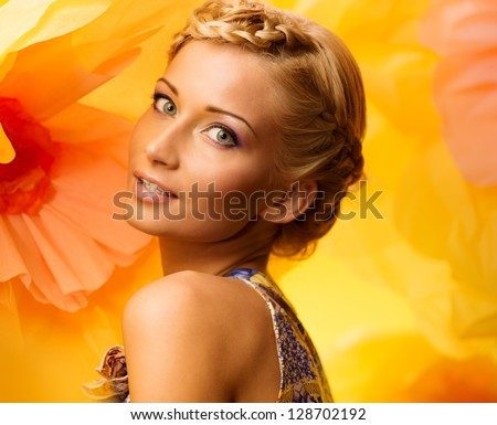 Beautiful young woman among big yellow flowers - stock photo