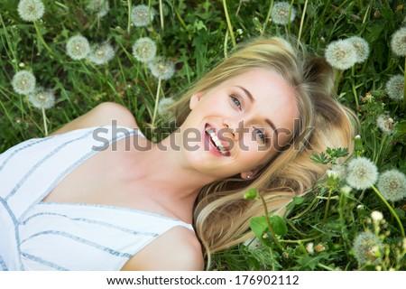 Beautiful young woman among dandelions - stock photo