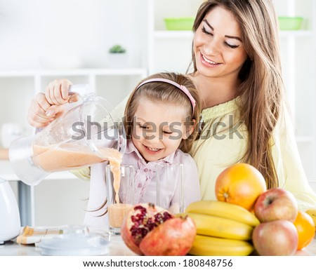 Beautiful young woman and cute little girl pouring juice from blender in the glass. In the kitchen concept. - stock photo