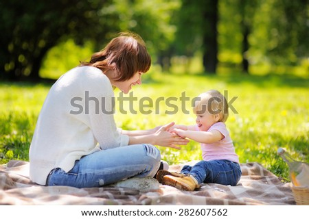 Beautiful young woman and her adorable little son having a picnic in sunny park  - stock photo