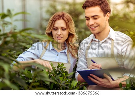 Beautiful young woman and man in aprons are making notes and smiling while examining plants in orangery