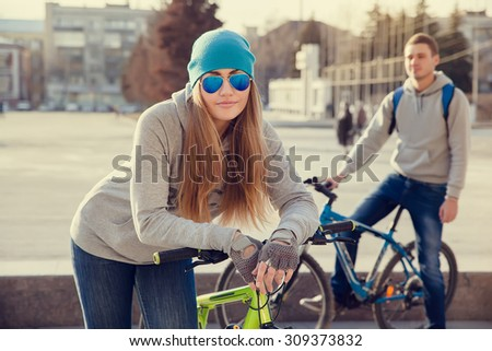 beautiful young woman and young man with bike in the city - stock photo