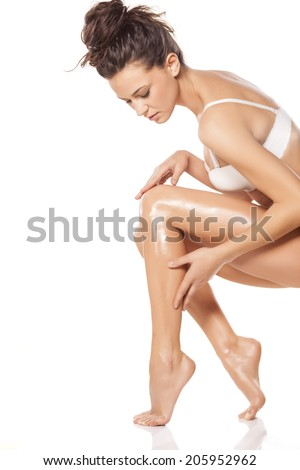 beautiful young woman apply lotion on her legs - stock photo