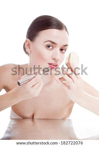 Beautiful young woman applying a glamour red lipstick on lips.