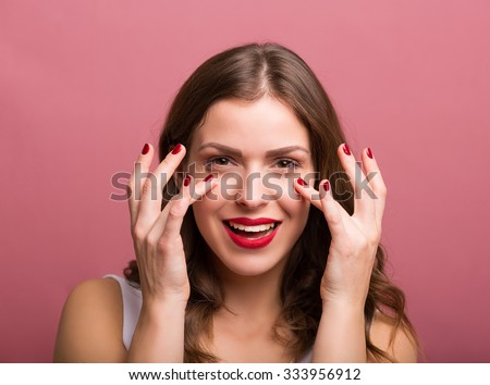 Beautiful young woman applying an eye cream - stock photo